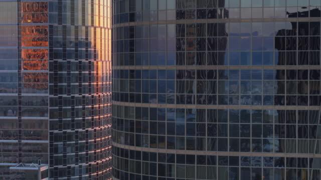 aufsteigender drohne schuss von gekrümmten modernen bürotürmen bei sonnenuntergang - wolkenkratzer stock-videos und b-roll-filmmaterial