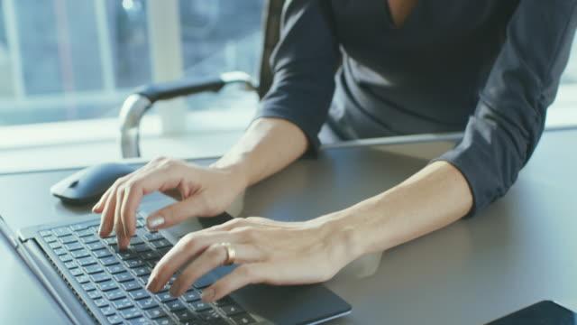 Toma de retrato ascendente de atractivo exitosa mujer de negocios trabajando en una portátil en su oficina con la ventana de vista de paisaje urbano. Fuerte independiente mujer CEO funciona empresa. - vídeo