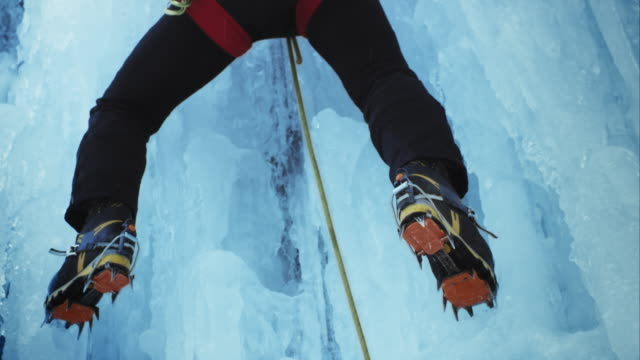 ascending the ice slope with crampons - eisklettern stock-videos und b-roll-filmmaterial