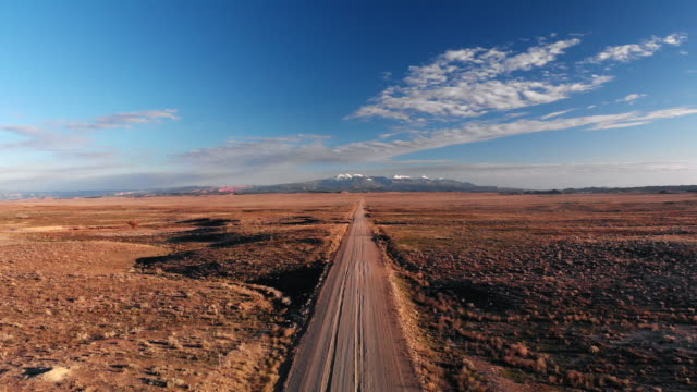 ascending trucking aerial drone shot of a vanishing point dirt road with mountains in the background outside of moab, utah with desert plains on either side underneath a blue sky at sunset/sunrise - wiejska droga filmów i materiałów b-roll