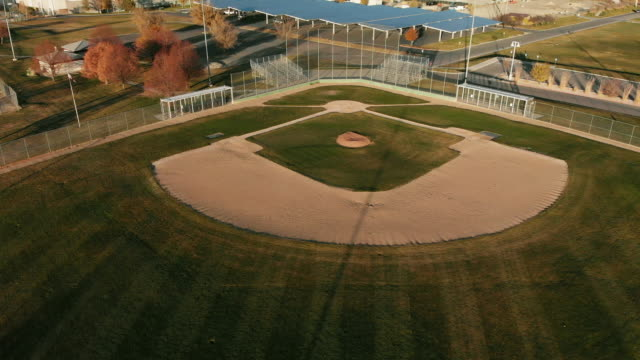 ascending trucking back aerial drone shot of an empty baseball diamond/field at sunset/sunrise on a sunny day - baseball stock videos and b-roll footage