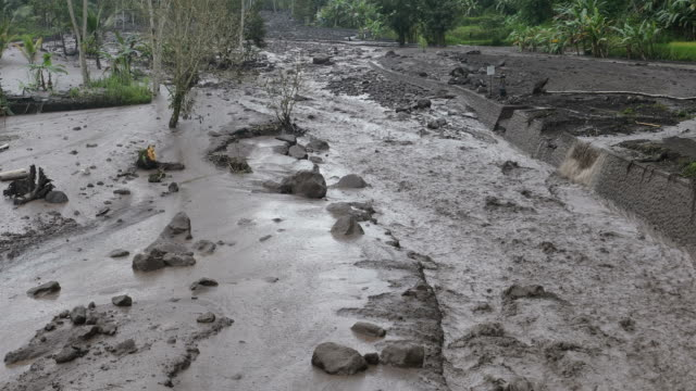 ash mud flooding from agung volcano in bali - pioggia torrenziale video stock e b–roll