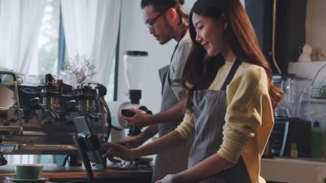 asia barista kellner verwenden tablet nehmen bestellung von kunden in café, café-besitzer schreiben getränke-bestellung an der theke-bar,essen und trinken geschäftskonzept, service mind concept.restaurant worker - bucht stock-videos und b-roll-filmmaterial