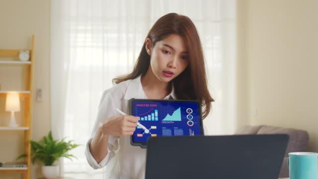 stockvideo's en b-roll-footage met de onderneemster van azië die laptop en tabletpresentatie aan collega's over plan in videovraag gebruikt terwijl het werken van huis bij woonkamer. - collega