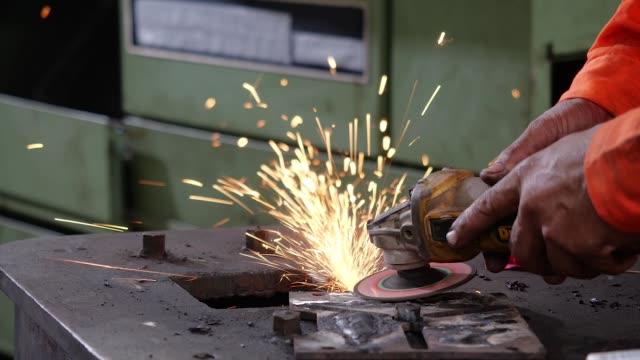 stockvideo's en b-roll-footage met azië ingenieur en werknemer die werkzaam zijn in de fabriek. close-up fabrieksarbeiders lassen in beschermende helmen - metaalbewerking