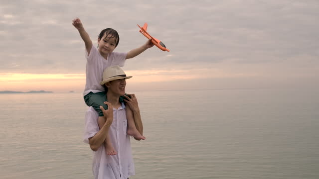 Asia father and son playing with airplane toy together at sunset happy family walking outdoors
