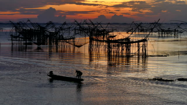 Asia Fishermen in the early morning golden light casting sow net fish video