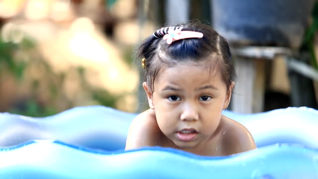 asia girl  playing in a paddling pool