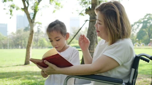 asia granddaughter and grandmother reading book at the park.slow motion - nonna e nipote camminare video stock e b–roll