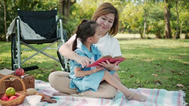 asia grandmother reading fairy tale to granddaughter at the park.slow motion - nonna e nipote camminare video stock e b–roll