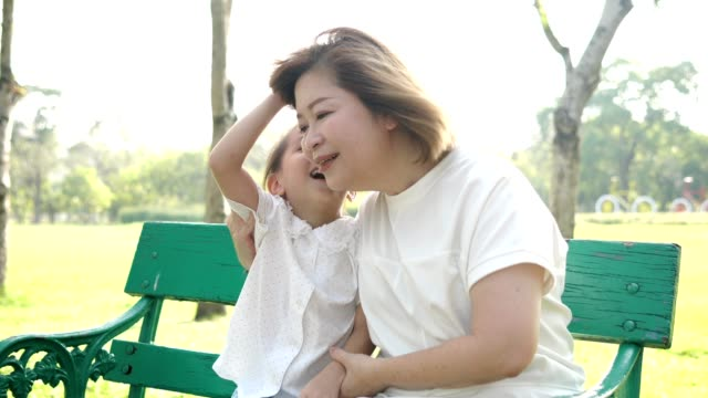 asia grandmother sit at the bench listen granddaughter talking at the park.slow motion - nonna e nipote camminare video stock e b–roll