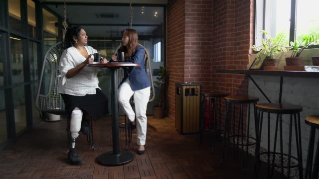 asia indian female Amputee colleague with prosthetic leg and chinese female colleague having conversation at office asia indian female Amputee colleague with prosthetic leg and chinese female colleague having conversation at office artificial limb stock videos & royalty-free footage
