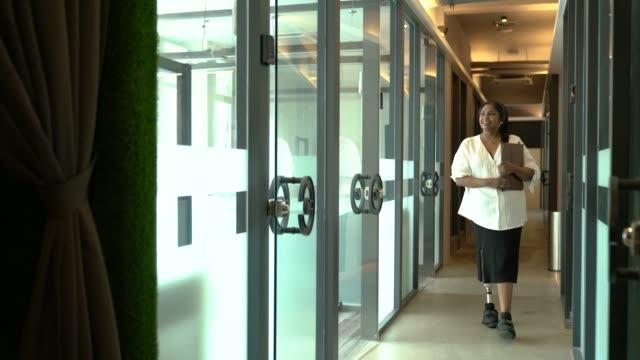 asien indiska kvinnliga amputee arbetstagare med protes ben promenader på kontoret - fysiskt funktionshinder bildbanksvideor och videomaterial från bakom kulisserna