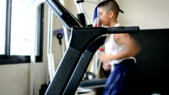 Asia kid running on the treadmill in a fitness. video