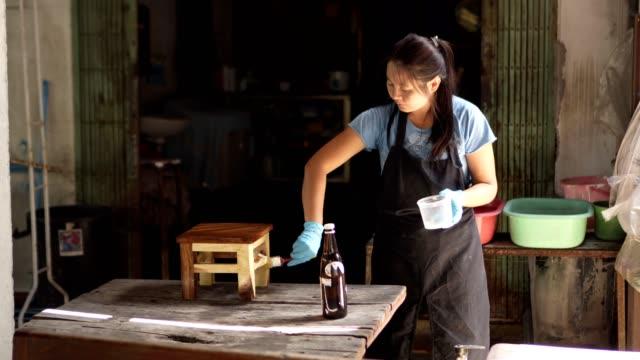 asia lady painting polyurethane wood chair - poliuretano polimero video stock e b–roll