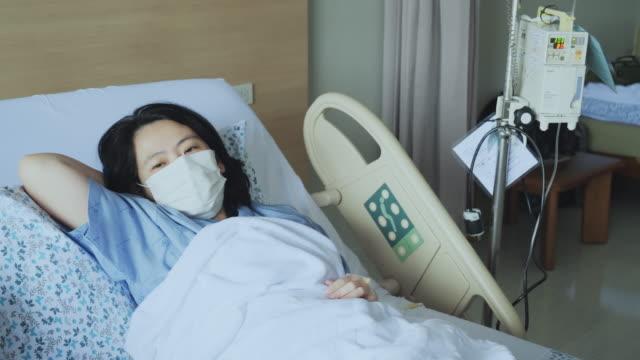 vídeos y material grabado en eventos de stock de asia mujer tos y enfermo con máscara en la cama del paciente. - repuesto