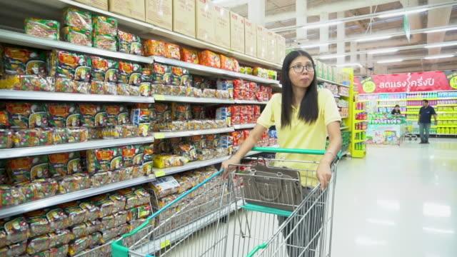 vídeos y material grabado en eventos de stock de asia mujer y compras en supermercado - snack aisle