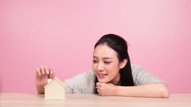 asia Woman hand putting money coin to house piggy bank
