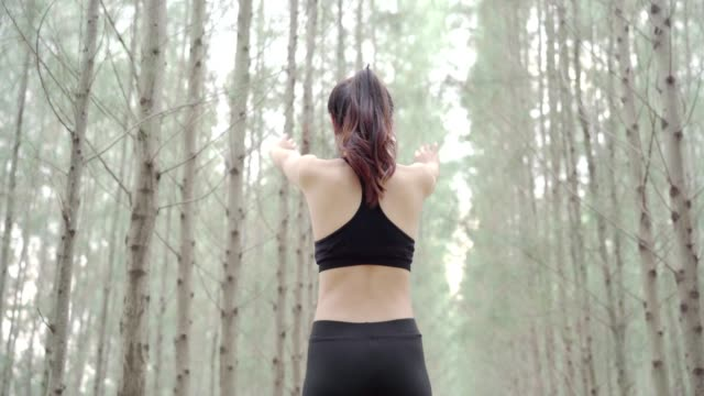 vídeos de stock e filmes b-roll de asia woman sporty resting relax muscles in the forest after runner cardio exercise workout, female happy enjoying freedom active healthy lifestyle stretching on summer at mountain rear view. - gmail
