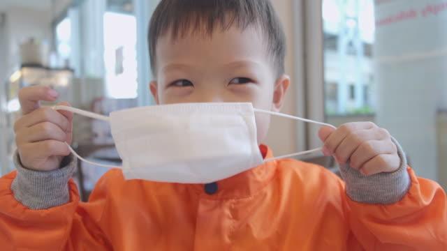 vidéos et rushes de asiatique 3 - 4 ans enfant en bas âge de garçon portant / a mis sur le masque médical protecteur contre des bactéries et des virus par lui-même - enfant masque
