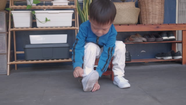 asian 3 years old toddler kindergarten kid sitting near shoe rack near front door of his house and concentrate on putting on his white shoes / sneakers - neonati maschi video stock e b–roll