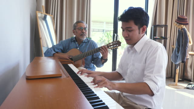 Asian adult son enjoy playing piano and senior father playing guitar together in living room at home Asian adult son enjoy playing piano and senior father playing guitar together in living room at home indian family stock videos & royalty-free footage