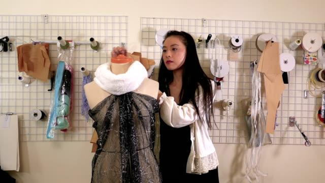 vídeos y material grabado en eventos de stock de diseñador de moda americano asiático en el trabajo en estudio, alfileres a tela sobre maniquí - bocetos de diseños de moda