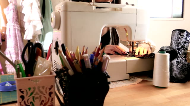 Asian American fashion designer sewing in studio, handheld video
