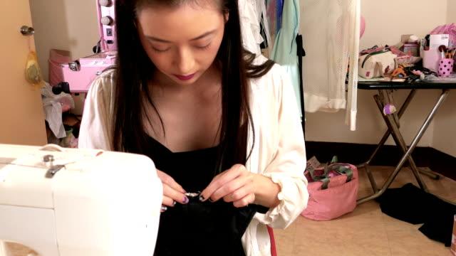vídeos y material grabado en eventos de stock de asiático americano diseñador de moda de costura en taller, movimiento de steadicam - bocetos de diseños de moda