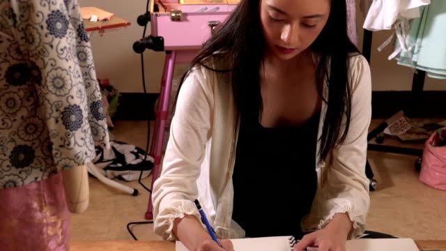 vídeos y material grabado en eventos de stock de asiático americano diseñador dibujar en estudio - bocetos de diseños de moda