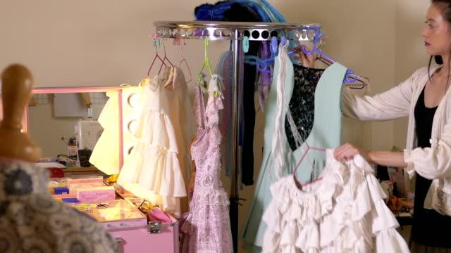 vídeos y material grabado en eventos de stock de vestidos de diseñador de moda americano asiático clasificación en rack - bocetos de diseños de moda