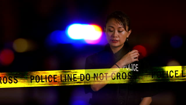 Asian American  female police officer calling in on radio from crime scene, Multiple exposure video