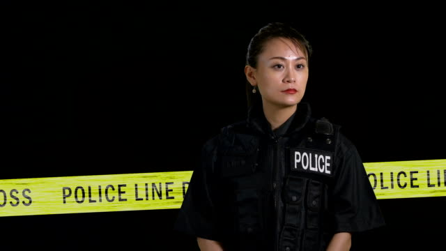 Asian American  female police officer calling in on radio from crime scene video