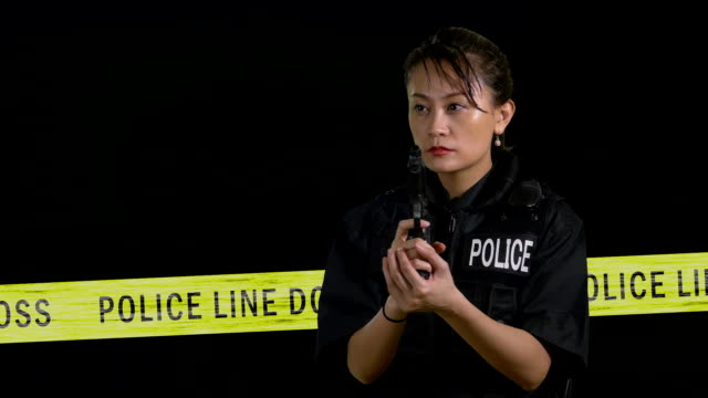 Asian American  female police officer pointing handgun with crime scene and flashing siren in background video