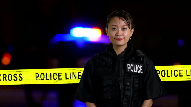Asian American policewoman smiling at crime scene with siren in background video
