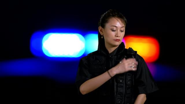 Asian American policewoman using radio at crime scene video