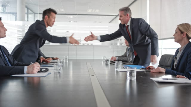 Asian and Caucasian businessman shaking hands after signing the contract in front of their team members in the conference room