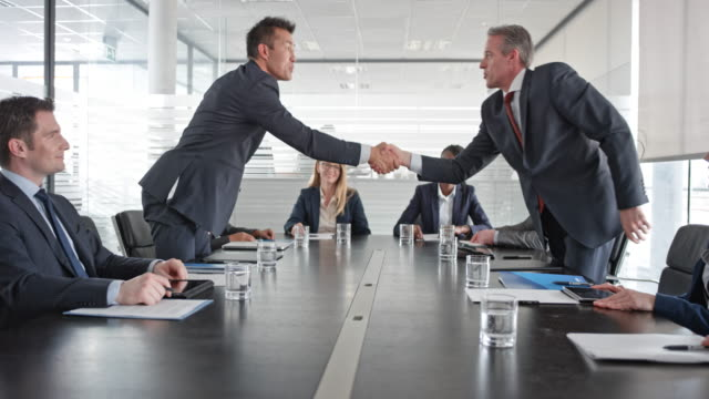 asian and caucasian businessman shaking hands in front of their project teams in the conference room - firma video stock e b–roll