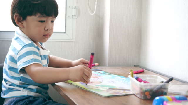 asian baby boy drawing and colouring in paper - matita colorata video stock e b–roll