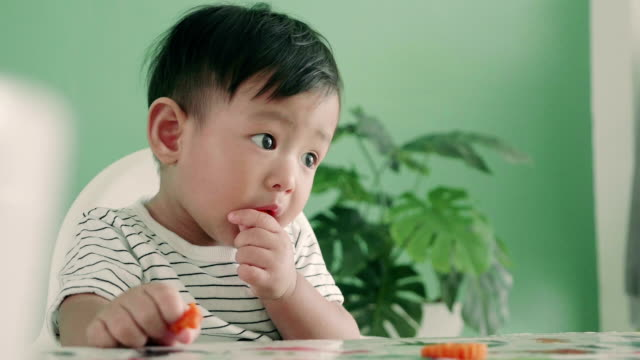 Asian baby boy eating a carrot, close up video