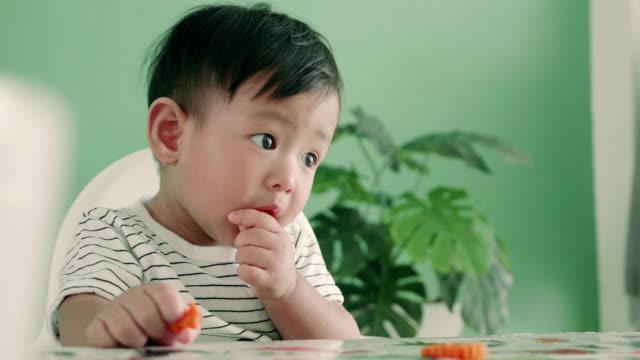 asiatisk pojke som äter en morot, närbild - morot bildbanksvideor och videomaterial från bakom kulisserna