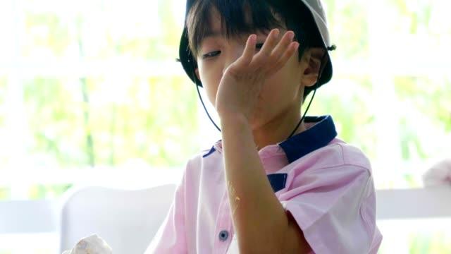 Asian baby boy eating cake