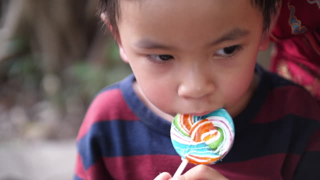 Asian baby boy eating candy