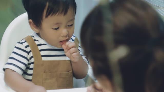 Asian baby boy feeding himself on high chair. video