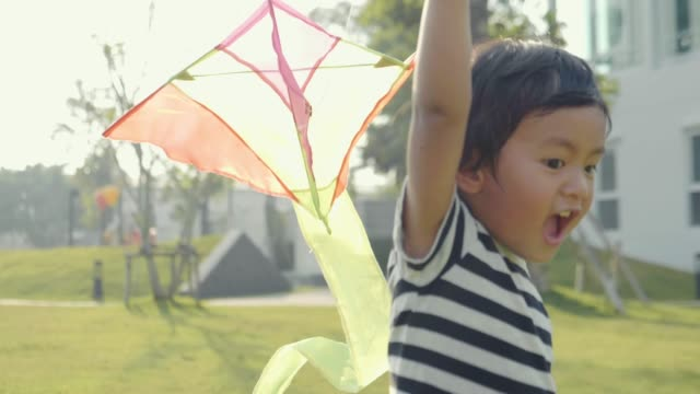 Asian Baby Boy Flying A Kite. Happy Memories Of His Young Days