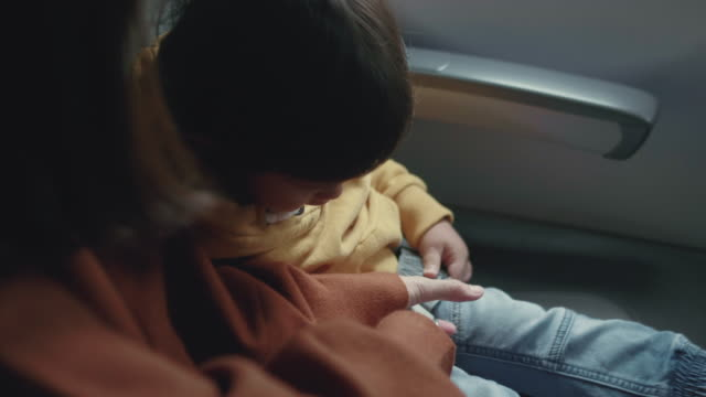 asian baby boy is fastening seat belt on airplane - sedili aereo video stock e b–roll
