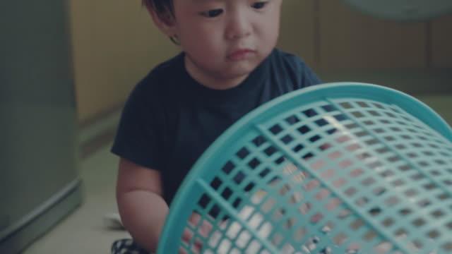 Asian baby boy learning to fold laundry at home A little baby boy learning to fold laundry at home. Bangkok, Thailand. laundry basket stock videos & royalty-free footage