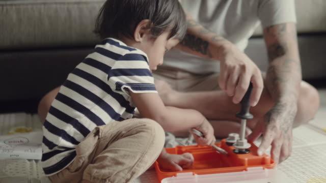 vidéos et rushes de garçon asiatique apprendre à jouer jouet avec son père. - tout petit