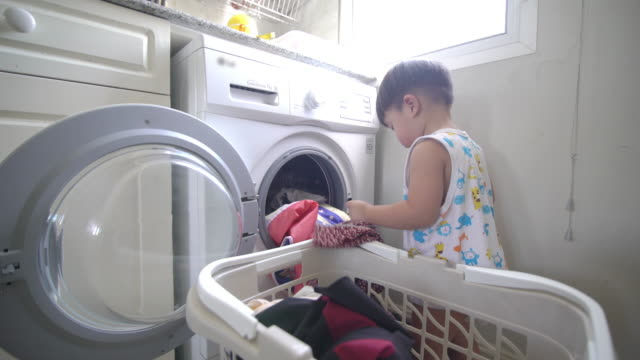 Asian baby boy loading clothes for washing clothes in an automatic laundry at home 4K Video by LS Hand-held Camera and selective focus with color grading of Asian baby boy loading clothes for washing clothes in an automatic laundry at home chores stock videos & royalty-free footage