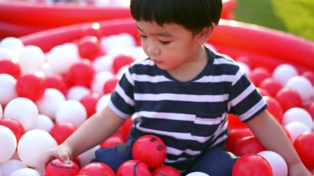 asian baby boy playing ball - solo neonati maschi video stock e b–roll